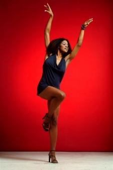 Photograph of a beautiful lady dancing with a red background