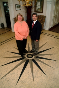 Photograph of a a man and a lady standing on a floor with a star